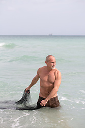 middle aged man using a fishing net in the ocean, Florida