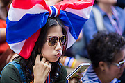 "20 DECEMBER 2013 - BANGKOK, THAILAND:  An anti-government protestor uses her smart phone during a demonstration in Bangkok. Many of the protestors are members of the Thai middle class, they are connected to the internet with smart phones and tablets. Thousands of anti-government protestors, supporters of the so called Peoples Democratic Reform Committee (PRDC), jammed the Silom area, the ""Wall Street"" of Bangkok, Friday as a part of the ongoing protests against the caretaker government of Yingluck Shinawatra. Yingluck dissolved the Thai Parliament earlier this month and called for national elections on Feb. 2, 2014. The protestors want the elections postponed and the caretaker government to step down. The Thai election commission ruled Friday that the election would go on dispite the protests.         PHOTO BY JACK KURTZ"