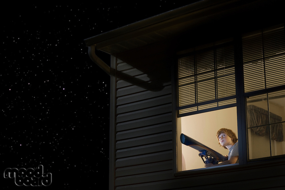 Teenage boy with telescope at open window looking at night sky