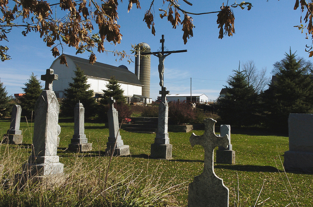DAIRYLAND CEMETERY — A crucifix and gravestones stand in contrast to a barn and silo behind St. Anthony Church Cemetery in rural Washington County, about 40 miles north of Milwaukee. All Souls Day, the commemoration of all the faithful departed, is Nov. 2. (Photo by Sam Lucero)