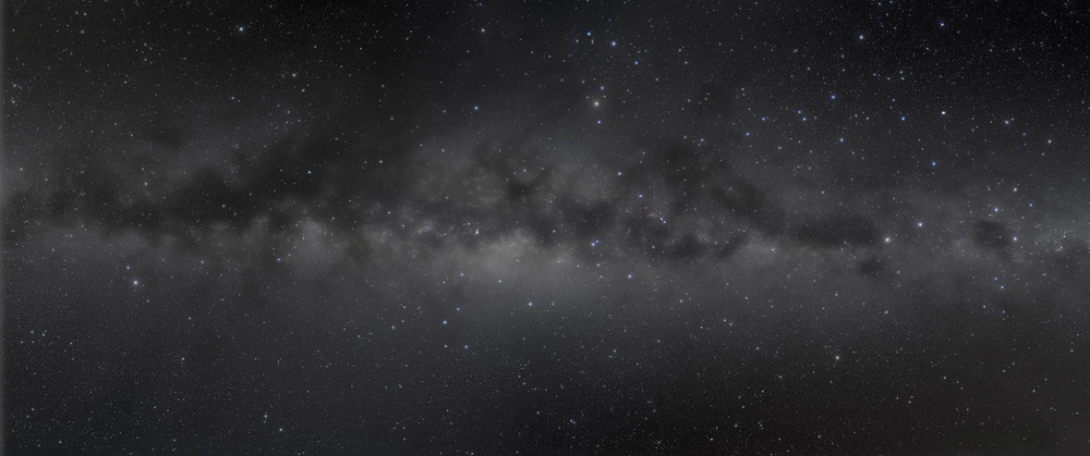 A panorama of the centre of the Galaxy portion of the southern hemisphere Milky Way, from Crux at right to Aquila at left. This was taken from Atacama Lodge near San Pedro de Atacama, Chile, on May 2, 2011. It is a 6-segment mosaic, each segment being 4 x 6 minutes + 1 x 6 minutes with a Kenko Softon filter, all at f/4 and ISO 800 with the Canon 5D MkII and Canon L-series 35m lens. Note the sweep of bright blue stars from Scorpius to Orion but angled above then across and below the Milky Way — this is Gould's Belt of new hot stars near us. This version of the image has been processed to make the view better resemble what you see with the unaided eye, in a largely monochrome and softer view than the colourful and high-contrast views commonly presented in astrophotos. Even at that there is more fine structure present in the Milky Way than the unaided eye usually sees, though binoculars beging to reveal that smaller detail. I have left some colours in some stars and in the foreground of landscape scenes.