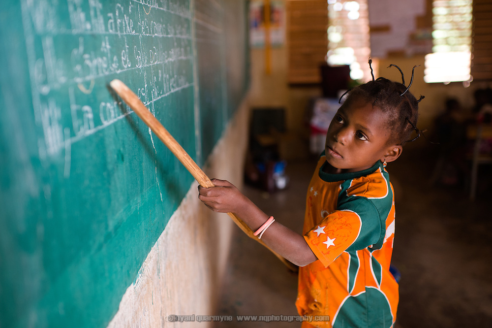 Adjara Ouattara (8) pointing out words as she reads them off the blackboard at a school in village of Toussiana in the Hauts-Bassins region of Burkina Faso, on 22 February 2016.