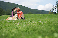 Couple with golden retriever sitting in meadow