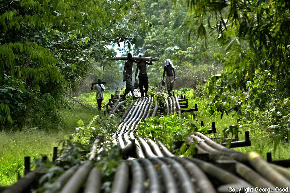 Local youths walk on oil pipeline belonging to Shell oil company on their way back from the farm in Utorogun, Nigeria, Sunday, March 5, 2006.Militants from the Movement for the Emancipation of the Niger Delta  (MEND)are still holding two U.S. hostages and one Briton.The crisis in the region has destrupted oil supply in the country which has help increase the price of oil in the past weeks(AP Photo/George Osodi)
