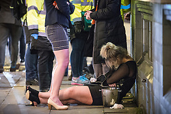 "© Licensed to London News Pictures . 19/12/2015 . Manchester , UK . A woman lies slouched on the pavement . Revellers in Manchester enjoy "" Mad Friday "" - also known as "" Black Eye Friday "" - the day on which emergency services in Britain are typically at their busiest , as people head out for parties and drinks to celebrate Christmas . Photo credit : Joel Goodman/LNP"