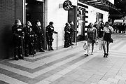 Weekend shoppers walk past police officers at the Freedom Rally at Westlake Park. Seattle, WA. August 13, 2017.