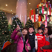 Two women and two kids take a selfie using a selfie stick in Times Square at Christmas time with Christmas decorations in the back ground. 7 million people live on 1,104km square, making it Hong Kong the most vertical city in the world.
