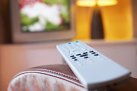 Remote control lying on armchair with television turned on in background close-up
