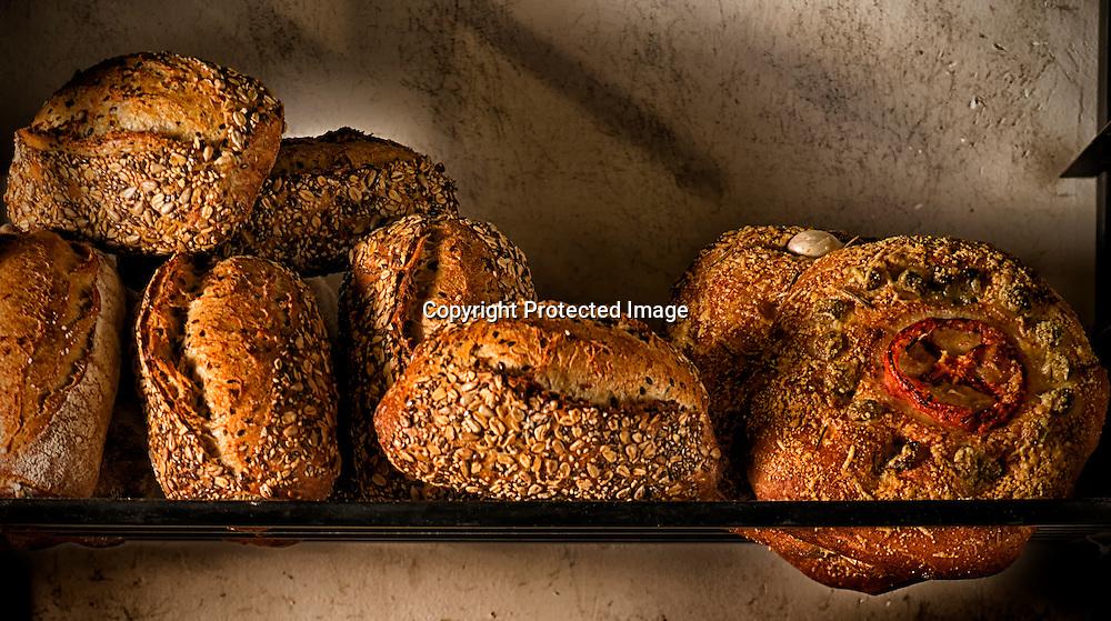 Sourdough loaves on a rack at an artisan bakery.