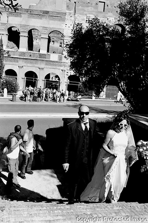 A newly married couple walking up some steps. The Coliseum can be seen in the backround.