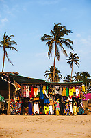 Palm trees and small shops along Anjuna Beach in northern Goa, India.