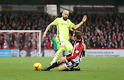 Brentford midfielder John Swift tackles Brighton defender, Bruno Saltor (2) during the Sky Bet Championship match between Brentford and Brighton and Hove Albion at Griffin Park, London, England on 26 December 2015.