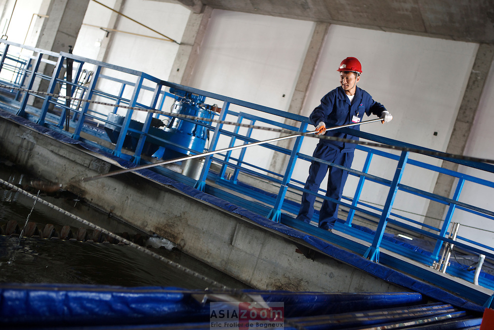 Employee perfoming daily cleaning on the Multiflo Lamella Stettler at Veolia Water's Maidao WWP in Qingdao, Chiina 2007