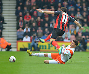 AFC Bournemouth's Charlie Daniels is tackled  during the Sky Bet Championship match between Bournemouth and Blackpool at the Goldsands Stadium, Bournemouth, England on 14 March 2015. Photo by Mark Davies.