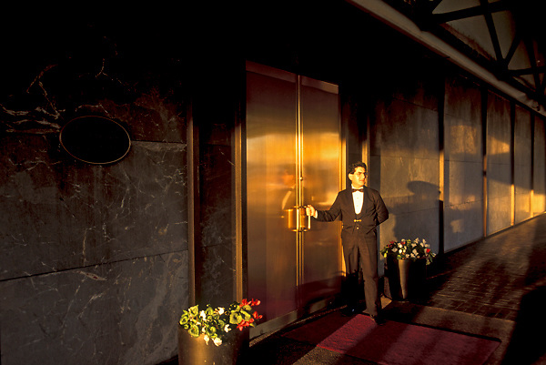 Stock photo of a door man ready to open the entrance to an upscale Houston establishment.