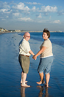 Senior couple walking on beach, looking back