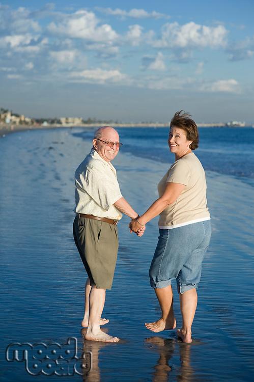 Senior couple walking on beach, looking back