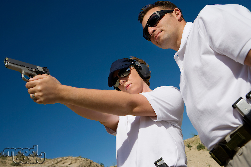 Instructor assisting woman aiming hand gun at firing range, low angle view