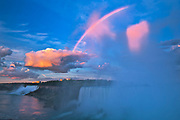 Storm clouds at sunrise with fog and rainbow as The Niagara River plunges over Niagara Falls.  Golden Horseshoe. Niagara Peninsula.<br /><br />Ontario<br />Canada