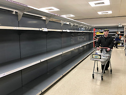 © Licensed to London News Pictures. 19/03/2020. Leeds UK. A pensioner walks past the empty shelves in the toilet roll isle of Sainsbury's in Colton, Leeds, as people continue to panic buy due to COVID 19.  Photo credit: Andrew McCaren/LNP