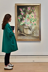 "© Licensed to London News Pictures. 01/08/2017. London, UK. A visitor views ""Lilacs"", 1914.  Preview of ""Matisse in the Studio"", at the Royal Academy of Arts, Piccadilly, the first exhibition to consider how the personal collection of treasured objects of Henri Matisse were both subject matter and inspiration for his work.  Around 35 objects are displayed alongside 65 of Matisse's paintings, sculptures, drawings, prints and cut-outs.  The exhibition runs 5 August to 12 November 2017.  Photo credit : Stephen Chung/LNP"