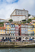 Colourful riverside balconied tiled homes and cafes in bright colours in Ribeira by the River Douro in Porto, Portugal