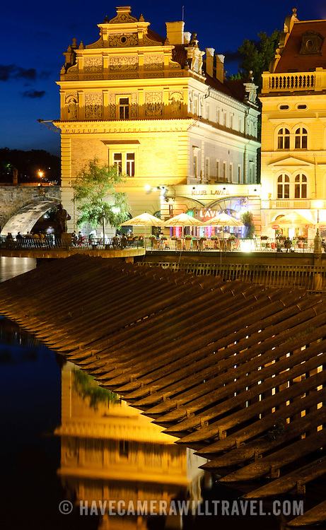 Buildings on the Vltava River with reflection on the water. This is right next to the Charles Bridge.