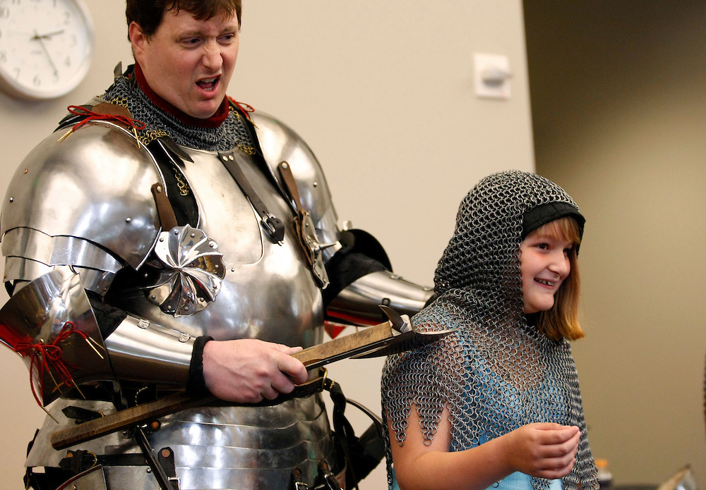 (20110611, Moline, Illinois)..Randy Cieszynski, or Sir Randall, shows off the strength of mail armor won by Jasmine Lohmeier, 9, of Bettendorf, IA during a presentation on medieval armor for kids aged 5 and up at the Moline Library in Moline, Illinois on Saturday, June 11, 2011...Brooks Canaday, Moline Dispatch
