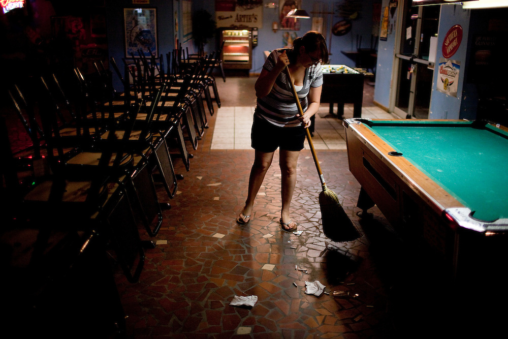 Bartender Heather Santiny, 23, sweeps up at Arties Sports Bar in Grand Isle, LA on June 23, 2010 where oil has reached land and killed the tourist industry. Manager Frankie Marullo said the bar would be packed with tourists during this time of the year but since the spill business has been slow and closes early.