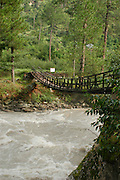 India, Kasol, Kullu District, Himachal Pradesh, Northern India A rope bridge over a river of gushing water