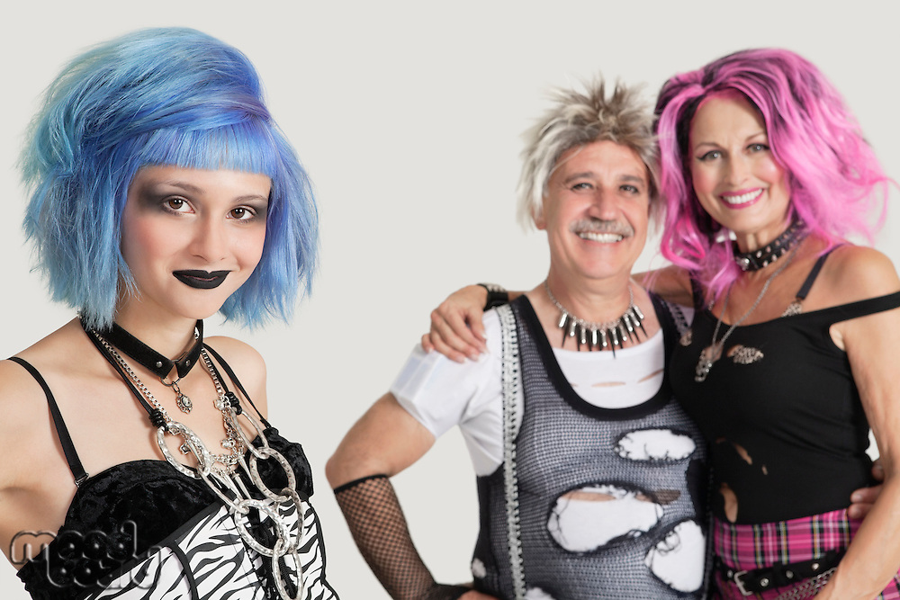 Portrait of punk male and females over gray background