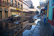Mexico City-Jan 14 : Street scene reflected in a puddle in the morning sunshine on 14 Jan at Av. República de Argentina, Mexico City