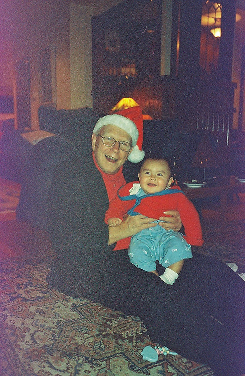 1. When was this photo taken?<br /> <br /> Christmas 2005<br /> <br /> 2. Where was this photo taken?<br /> <br /> In the living room of our home<br /> <br /> 3. Who took this photo?<br /> <br /> I did<br /> <br /> 4. What are we looking at here?<br /> <br /> It's the Christmas gift exchange and the first time my husband Carl has gotten to see his first grandchild, Marie, who was then about 7 months old.<br /> <br /> 5. How does this old photo make you feel?<br /> <br /> I have a mixture of happiness and great sorrow looking at this photo. Just looking at Carl, you can see how happy he was to have a little grand-daughter. He was thrilled! And you can see how physically able and mentally engaged he was. I remark on those things because 3 years later, in 2008, Carl would start to show signs of Lewy body dementia, a widespread yet under-recognized disease that robs a person of their physical and cognitive capacities. By Christmas of 2013, Carl would be dead. He was the love of my life and I devoted myself to his care during the 5 years of his illness, so this picture brings me pain and joy as I remember the exuberant man he was and yet know what fate is in store for him.<br /> <br /> 6. Is this what you expected to see?<br /> <br /> I was a bit afraid of what I'd discover on these rolls of film. Carl and I traveled a good deal and had many wonderful experiences, so I thought that these would be lost vacation photos. As much as I wanted to see them, I was afraid that seeing images of our happy times together would stab my heart as they reminded me of what I've lost.<br /> <br /> 7. Does this photo bring back any memories?<br /> <br /> This photo conjures up memories of a very happy holiday gathering for our family. At this particular moment, Carl's children all seemed to be settled and happy. Carl and I were in a home we had renovated (and the renovation was finished!). Everything then was going very well.<br /> <br /> 8. How do you think others will respond to this pho