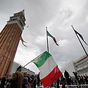 VENICE, ITALY - MARCH 17:  A man walks with an Italian national flag in St Mark Squar on the day of the celebrations for the 150th anniversary of Italy's unification on March 17, 2011 in Venice, Italy. Events in various Italian cities will celebrate the 150th anniversary of Italy's unification until the end of the year. National Festivity begins on March 17.
