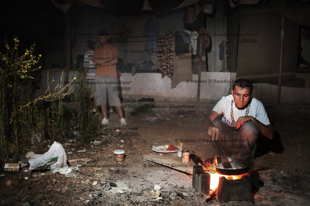 Ragazzi Afgani accampati in una zona di Roma fghan boy cooks his dinner over a fire
