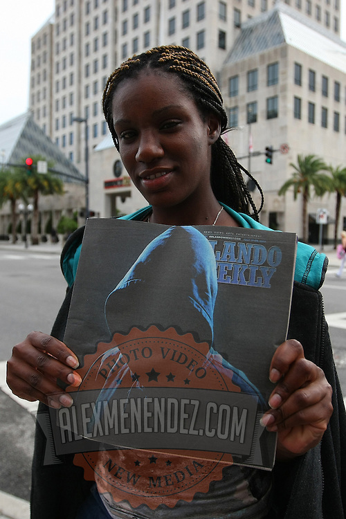"""A protester holds up a copy of the Orlando Weekly magazine featuring the look of Trayvon Martin, during the No Justice No Peace- """"March Against Gun Violence""""  walk from Lake Eola in downtown Orlando, to the Orange County Courthouse on Wednesday, July 17, 2013. The march was organized by the Modarres Law Firm and Orlando attorney Natalie Jackson, one of the attorneys for Trayvon Martins parents. (AP Photo/Alex Menendez)"""