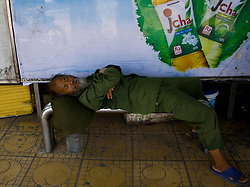 Vietnamese man sleeping on a bench at a bus stop. Hanoi, Vietnam, Asia