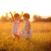 Young twin girls in white dresses play in a field  in Goa in the afternoon