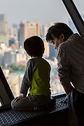 A little boy and his father stare out the window of the Bunkyo Civic Center Observation Deck at the metropolis below