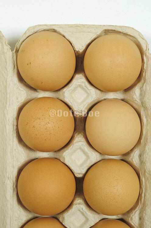 a dozen brown eggs in an egg carton
