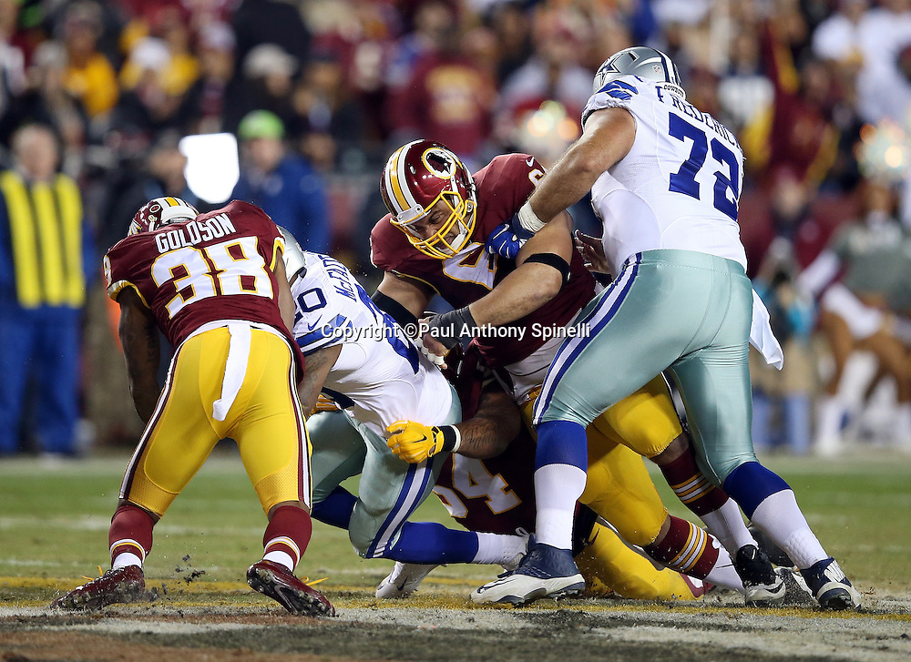 Dallas Cowboys running back Darren McFadden (20) gets gang tackled by Washington Redskins free safety Dashon Goldson (38) and Washington Redskins defensive end Kedric Golston (64) as he runs the ball during the 2015 week 13 regular season NFL football game against the Washington Redskins on Monday, Dec. 7, 2015 in Landover, Md. The Cowboys won the game 19-16. (©Paul Anthony Spinelli)