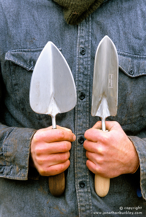 Man holding narrow and broad trowels