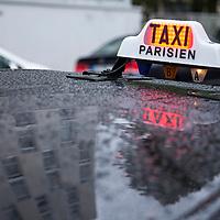France, Paris, Illuminated sign of Taxi Parisien in spring rain
