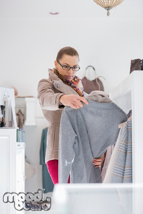 Woman choosing sweater in store