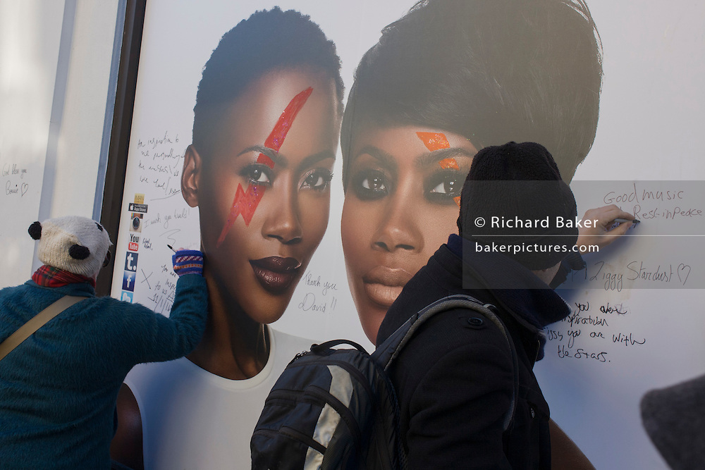 Fans of iconic English music artist David Bowie who died from Cancer at the age of 69 on Sunday 10th January, have written messages on the faces of black models from Bowie's wife's Iman's cosmetic ad with drawn Ziggy Stardust zigzag across their faces. Others gather to pay their respects at a makeshift shrine of flowers and tributes to the local boy from Brixton, south London. Commuters stopped-by before entering the nearby underground station to take pictures and silently remember their hero's great days playing the soundtracks of their childhoods.