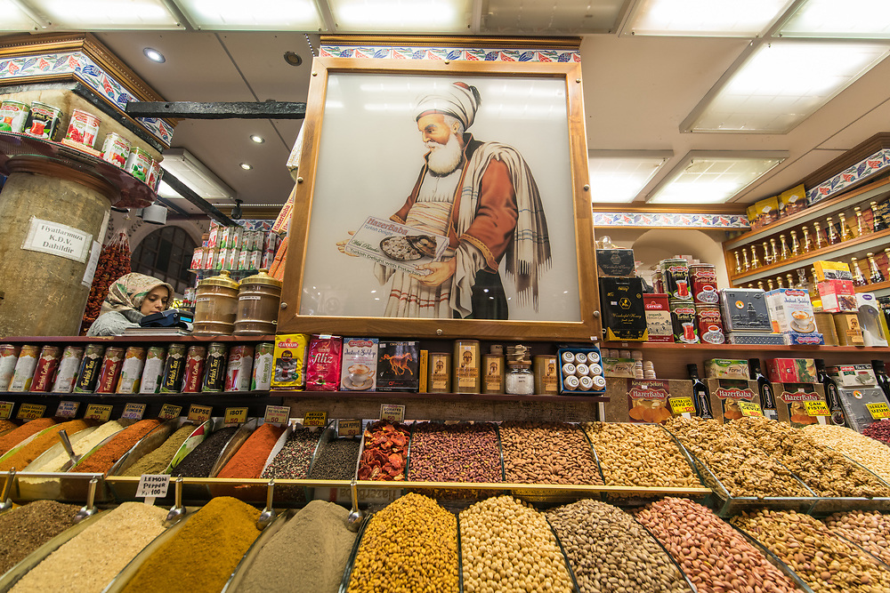 A sign above the spice bins at store depicts a Turkish man holding a box of Turkish delights, Istanbul Spice bazaar in Turkey