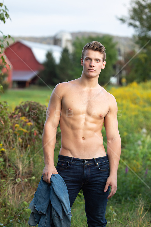 sexy shirtless man standing in a field by a barn
