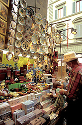 Florence, Italy:  A tourist shops at a stationery stall in the city's famous Straw Market (Mercato Nuovo).