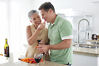 Woman feeding pepper to husband in kitchen