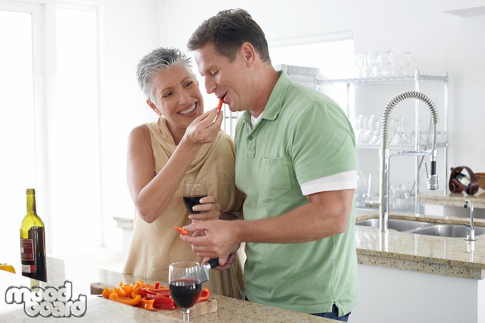 Woman feeding pepper to husband in kitchen